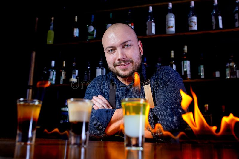 Fiery show at the bar. The bartender makes hot alcoholic cocktail and ignites bar. Bartender prepares a fiery cocktail. Fire on bar royalty free stock images
