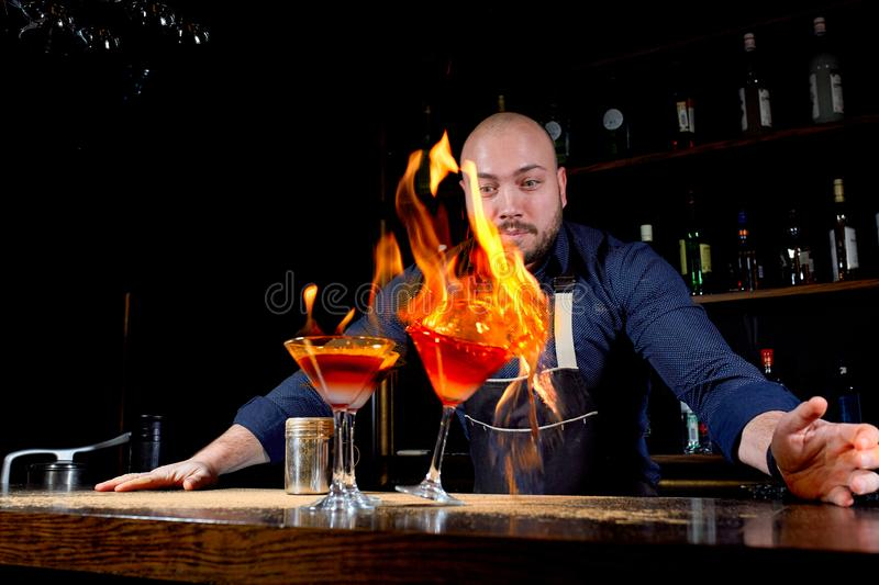 Fiery show at the bar. The bartender makes hot alcoholic cocktail and ignites bar. Bartender prepares a fiery cocktail. Fire on bar stock photos