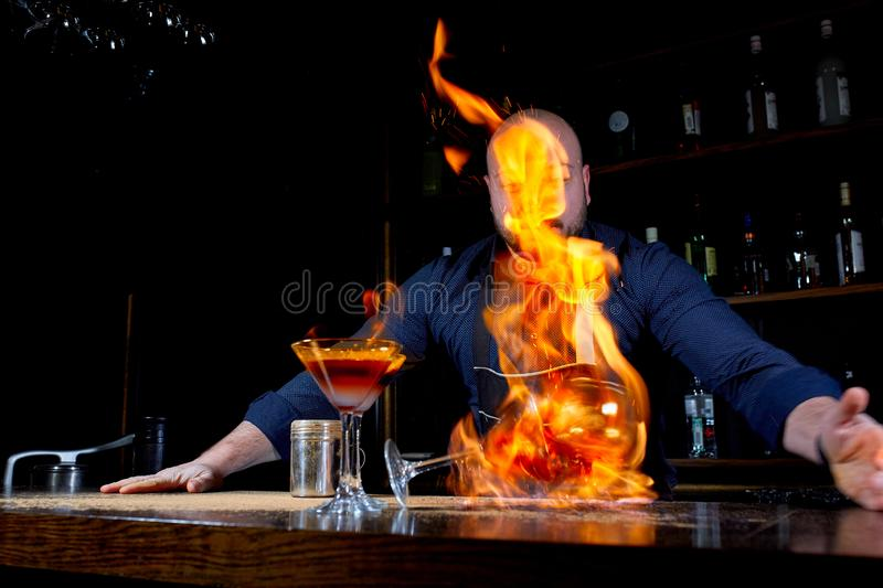 Fiery show at the bar. The bartender makes hot alcoholic cocktail and ignites bar. Bartender prepares a fiery cocktail. Fire on bar stock image