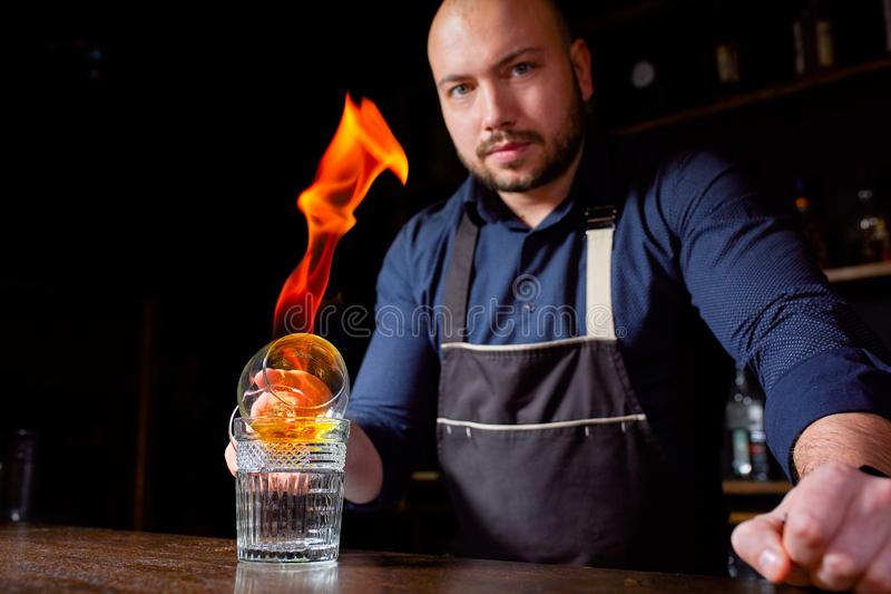 Fiery show at the bar. The bartender makes hot alcoholic cocktail and ignites bar. Bartender prepares a fiery cocktail. Fire on bar stock photography