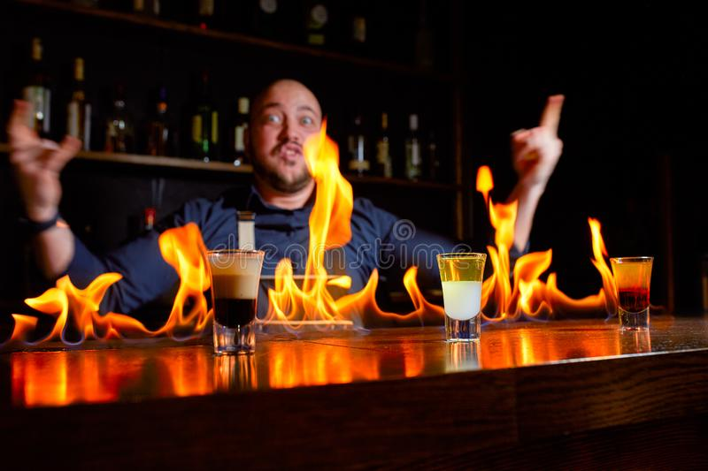 Fiery show at the bar. The bartender makes hot alcoholic cocktail and ignites bar. Bartender prepares a fiery cocktail. Fire on bar stock photo