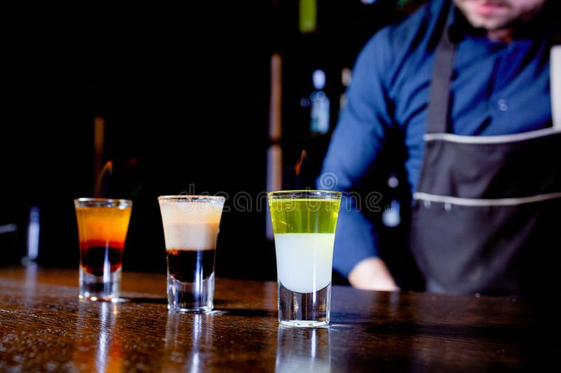 Fiery show at the bar. The bartender makes hot alcoholic cocktail and ignites bar. Bartender prepares a fiery cocktail. Fire on bar stock images