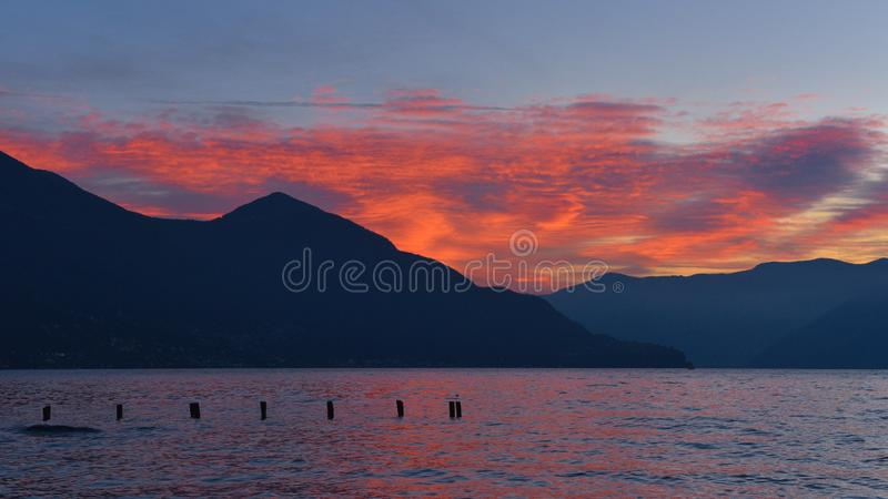 Fiery sky of red clouds at sunset on the lake. In january stock photos