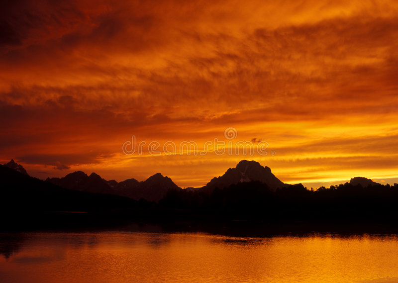 Fiery Sunset Over Teton. Fiery sunset over the Teton Mountains and the Snake River, located in the Grand Teton National Park in Wyoming (USA royalty free stock photos