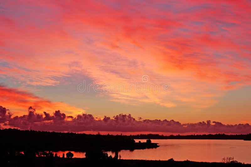 fiery sunset on river with silhouette land, perth stock photos
