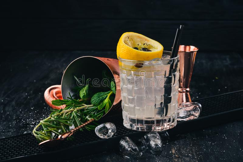 Fiesta Alcoholic Cocktail. Sambuca liqueur, tonic, lemon. On a black wooden background stock image