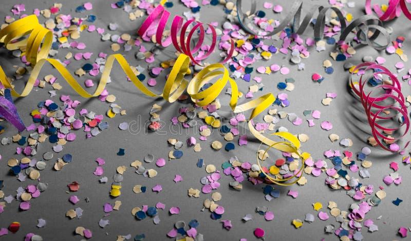 Fiesta del carnaval o de cumpleaños, confeti y serpentinas en fondo gris fotos de archivo
