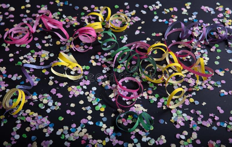 Fiesta del carnaval o de cumpleaños, confeti y serpentinas en fondo negro imagenes de archivo