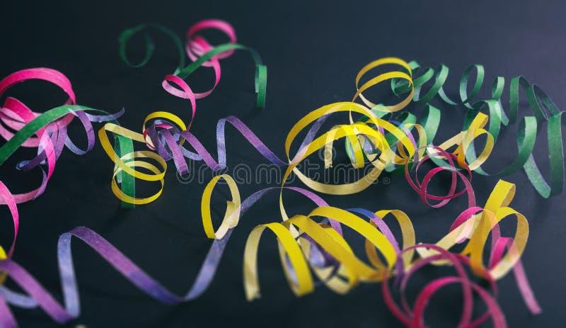 Fiesta del carnaval o de cumpleaños, serpentinas en fondo negro imágenes de archivo libres de regalías
