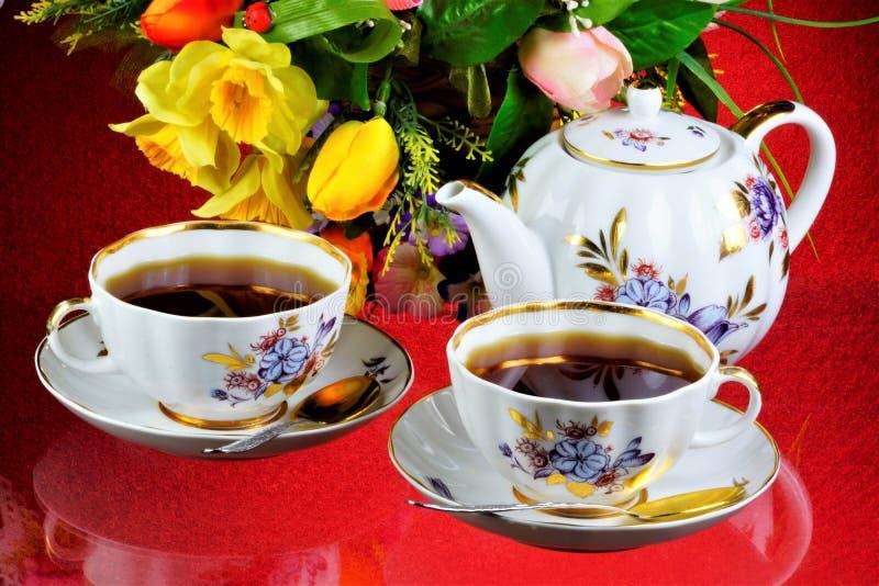 Fiesta del té - té en tazas, tetera, flores del jardín en un día de verano El té diario es una bebida deliciosa, popular, sana, q foto de archivo libre de regalías