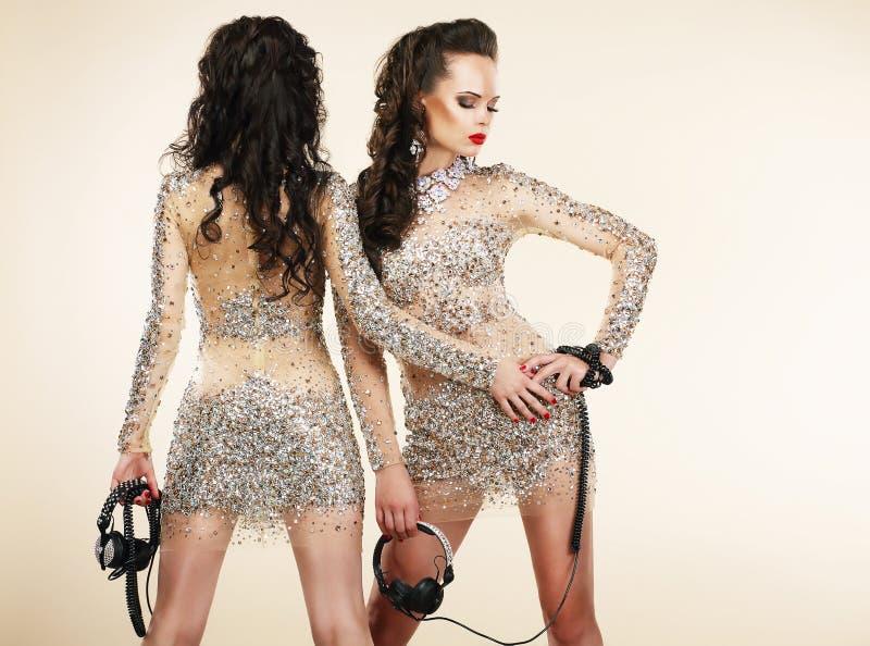 Fiesta. Ir de discotecas. Dos mujeres en vestidos de plata brillantes con los diamantes artificiales foto de archivo libre de regalías