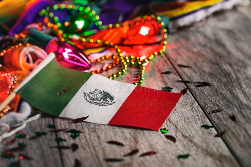 Fiesta: Mexicansk flagga i fokus med glödande partiljus royaltyfri bild