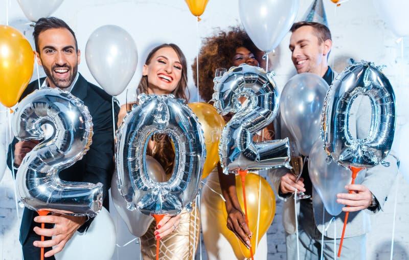 Fiesteros mujeres y hombres celebrando los nuevos años, víspera de 2020 imágenes de archivo libres de regalías