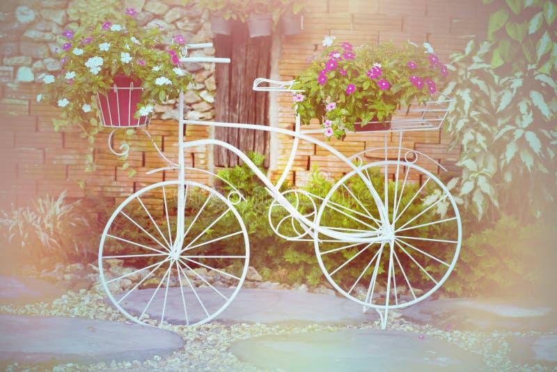 Fiets die met bloemen in de tuin wordt verfraaid royalty-vrije stock afbeelding