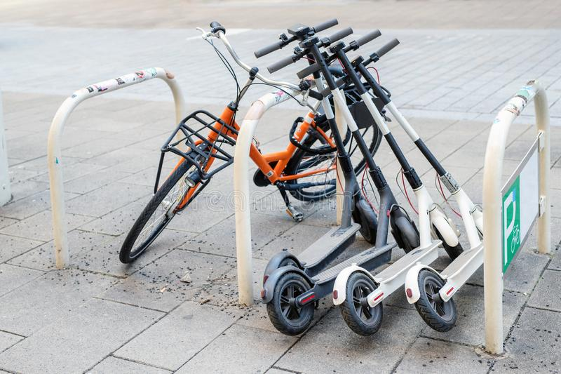 Fiets en elektrische die autopedden op stadsstraat wordt geparkeerd De dienst van de het vervoerhuur van de zelfbedieningsstraat  stock foto