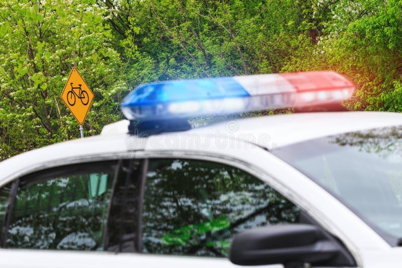 Fiets of fietsverkeersteken met selectieve nadruk & politiewagen met stock afbeeldingen