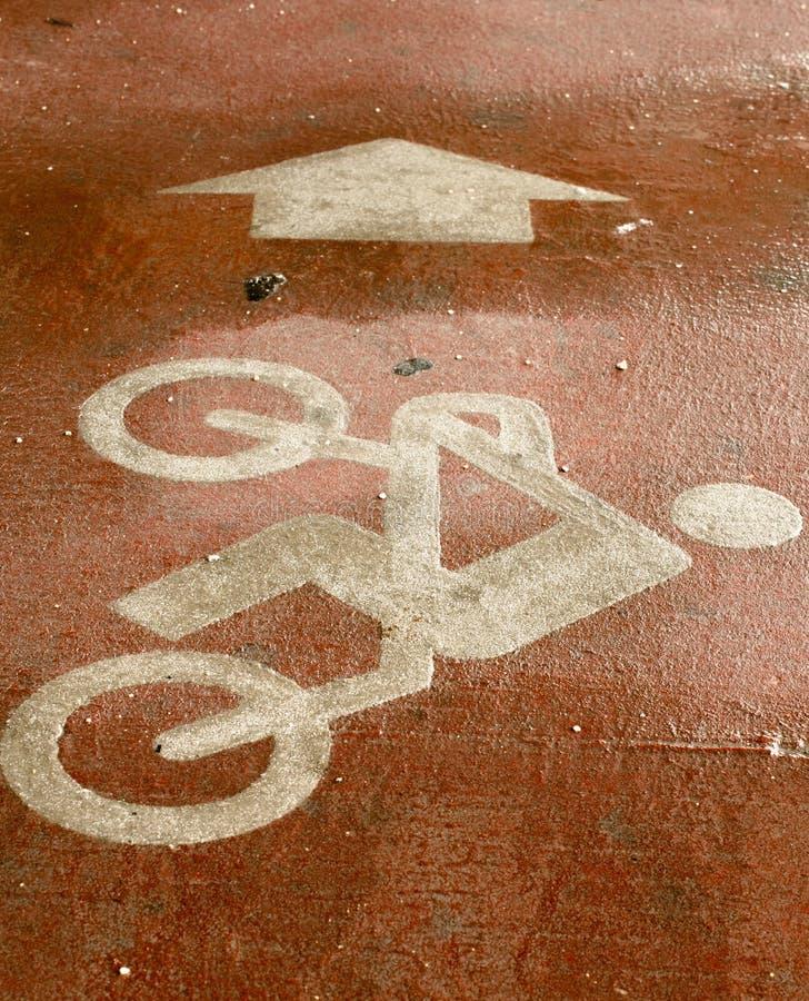 Fiets met bestuurdersteken dat op de vloer met pijl wordt geschilderd stock afbeelding
