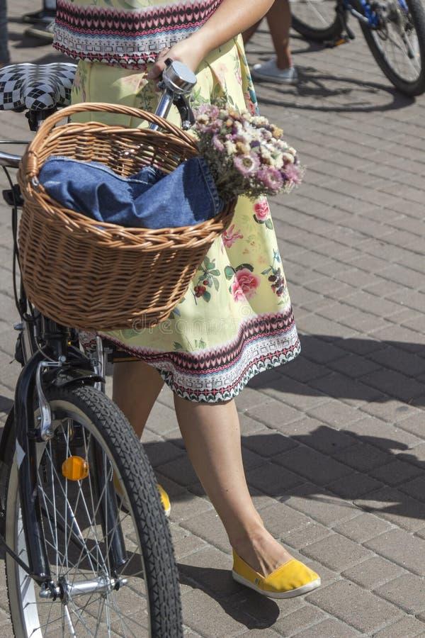 Fiets met mand van bloemen De vrouw in heldere kleren houdt de sturen royalty-vrije stock afbeeldingen
