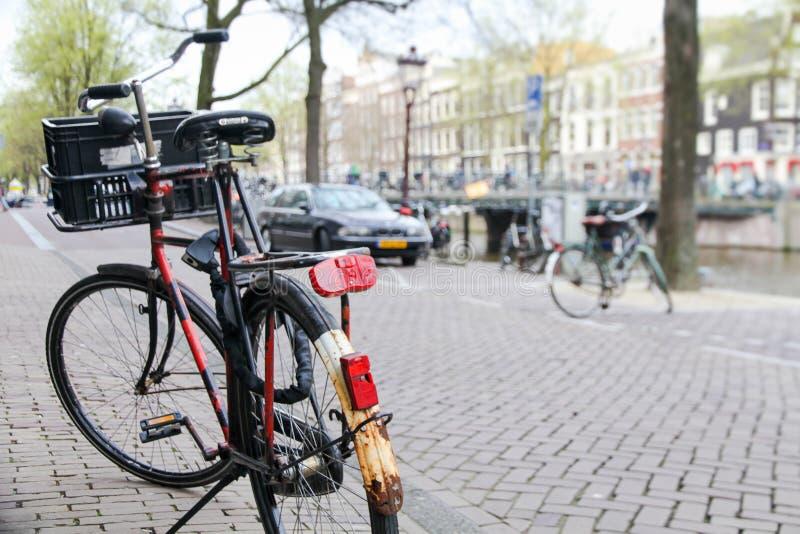 Fiets op de straat in de voorgrond met een typische kanaal en een architectuur van Amsterdam, Nederland wordt geparkeerd dat royalty-vrije stock afbeelding