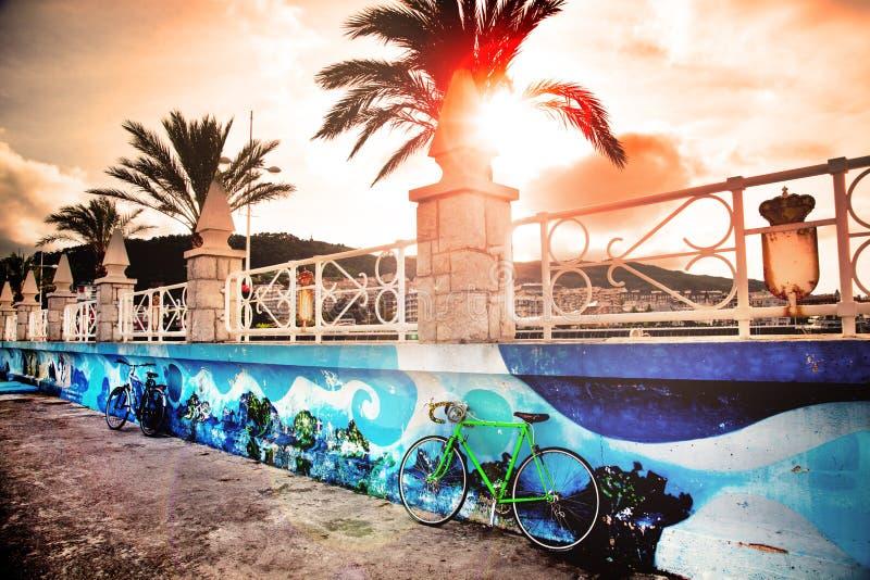 Fiets op de waterkant in kustdorp met een mooie zonsonderganghemel en palmen stock foto