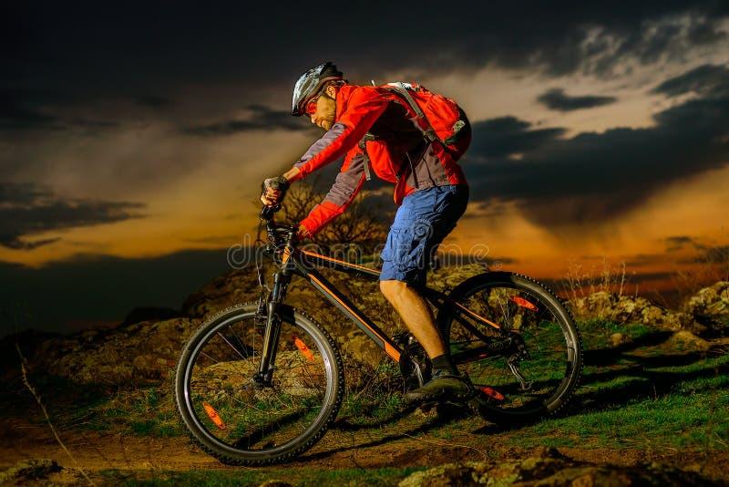 Fiets van de fietser de Berijdende Berg op de Lente Rocky Trail bij Mooie Zonsondergang Extreme Sporten en Avonturenconcept stock foto