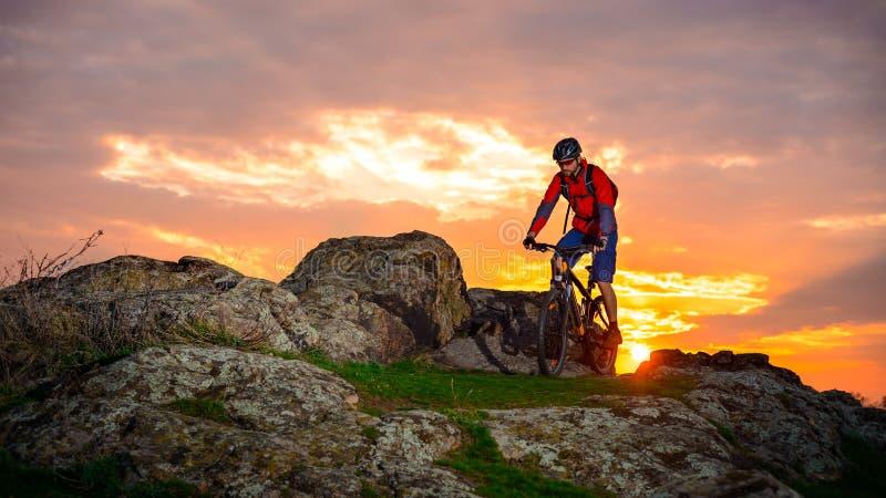 Fiets van de fietser de Berijdende Berg op de Lente Rocky Trail bij Mooie Zonsondergang Extreme Sporten en Avonturenconcept royalty-vrije stock foto's