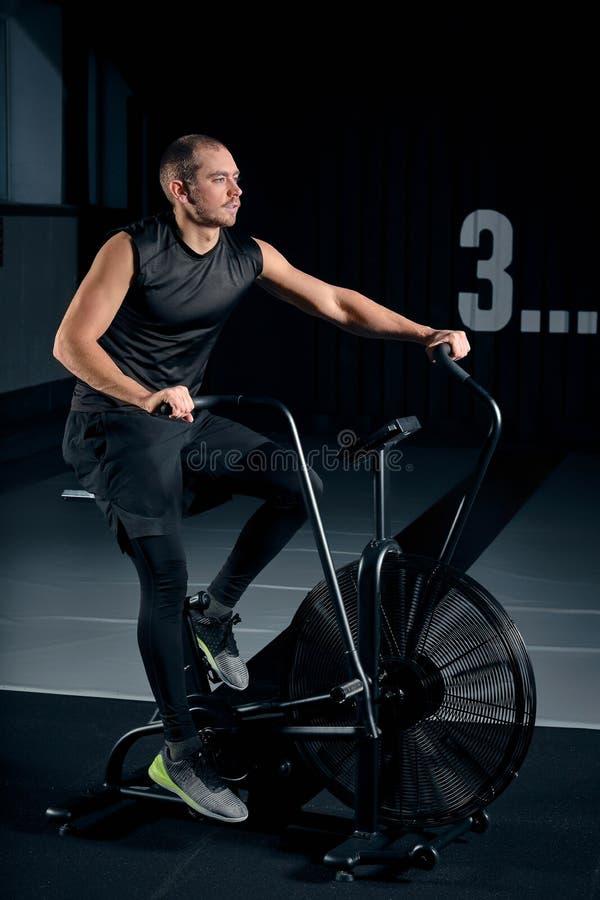 Fiets van de geschiktheids de mannelijke gebruikende lucht voor cardiotraining bij Functionele opleidingsgymnastiek royalty-vrije stock afbeelding