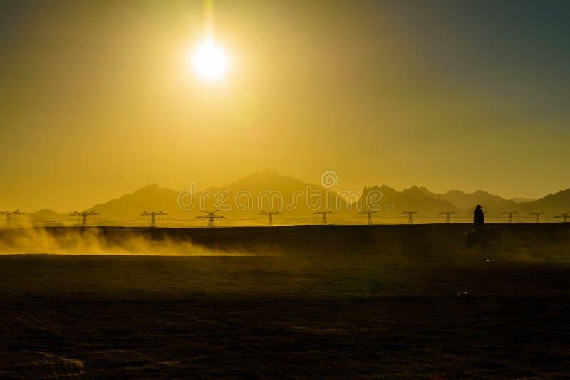Fiets van de onherkenbare mensen de drijfvierling tijdens safarireis bij zonsondergang in Arabische woestijn niet verre van de Hu royalty-vrije stock foto's