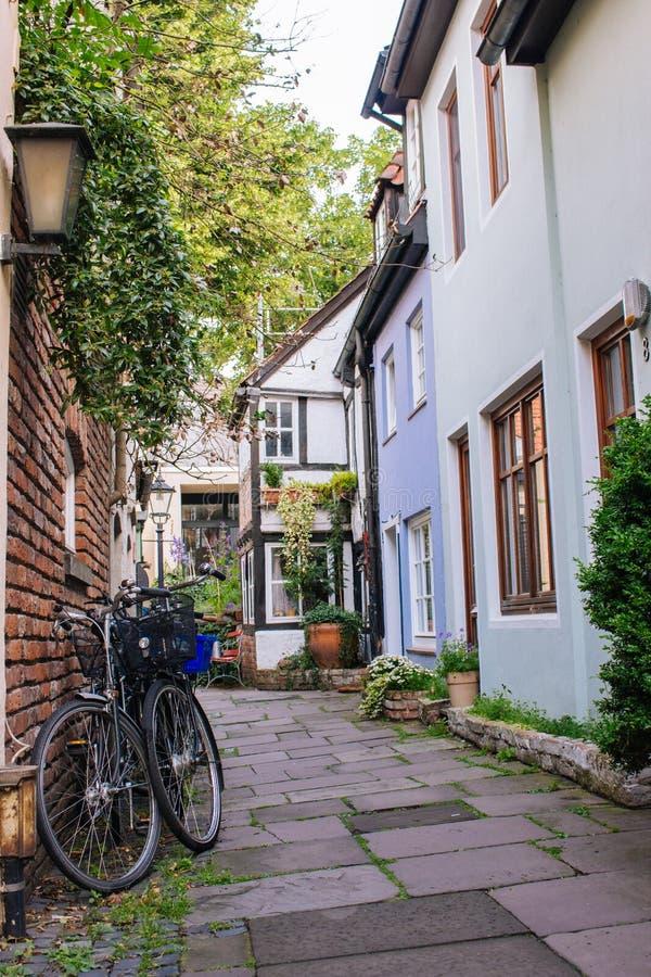 Fietsen en bomen in comfortabele binnenplaats De zomerterras met fietsen Fietsen voor oud huis Traditionele buitenkant in Europa stock fotografie