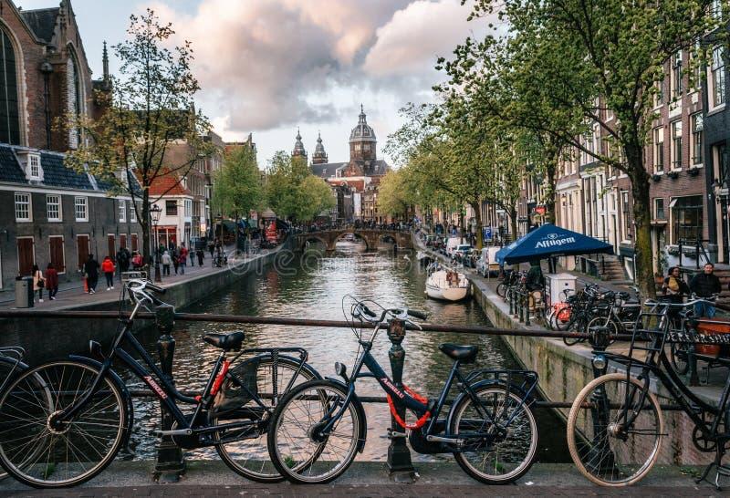 Fietsen langs de brug worden geparkeerd die Kanaal van Amsterdam stock foto