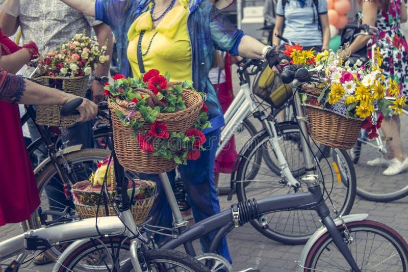 Fietsen met manden van bloemen De vrouwen in heldere kleren houden de sturen royalty-vrije stock foto
