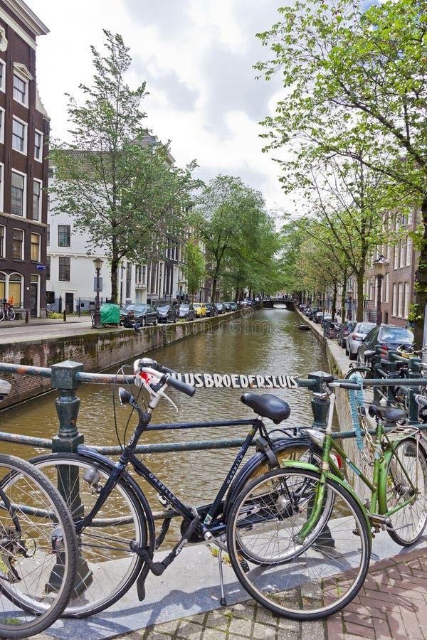 Fietsen op Paulusbroedersluis-brug in Amsterdam worden geparkeerd dat stock afbeeldingen