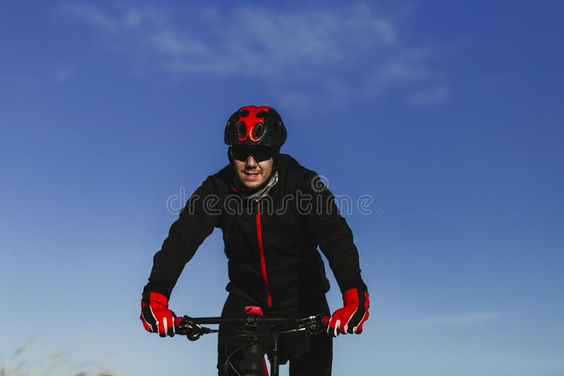 Fietser die de Fiets onderaan Rocky Hill berijden bij Zonsondergang Extreem Sportconcept stock foto