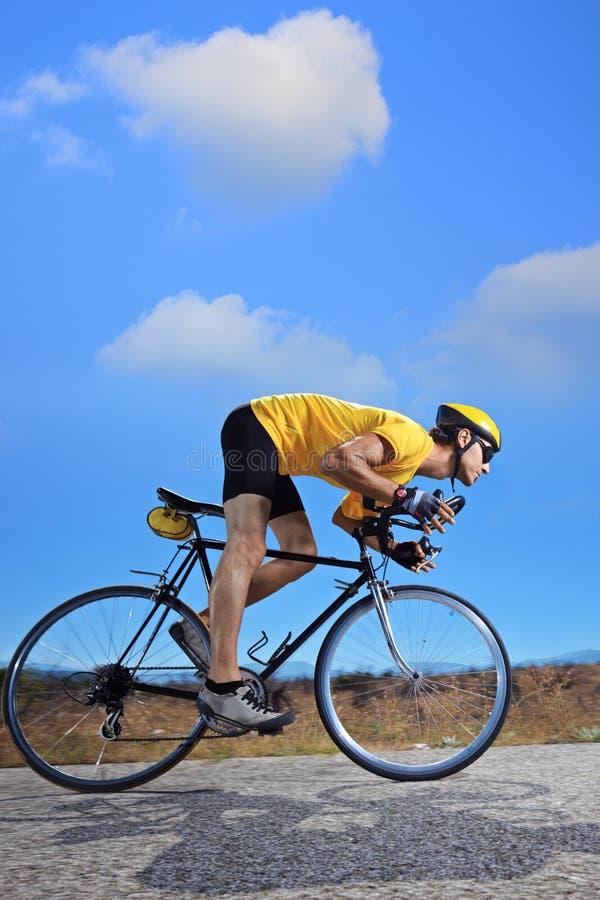 Fietser die een fiets berijdt op een open weg stock afbeeldingen
