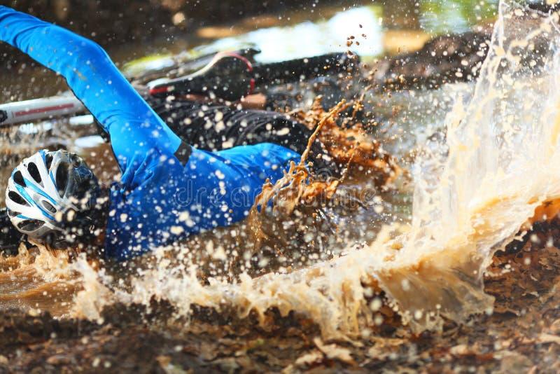 Fietser die in een pool van vuil water valt royalty-vrije stock foto's