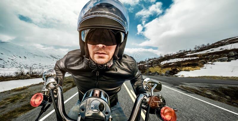 Fietser die in helm en leerjasje op bergkronkelweg rennen royalty-vrije stock fotografie