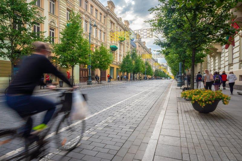 Fietser die vlug door op de belangrijkste commerciële straat van Vilnius overgaan stock fotografie