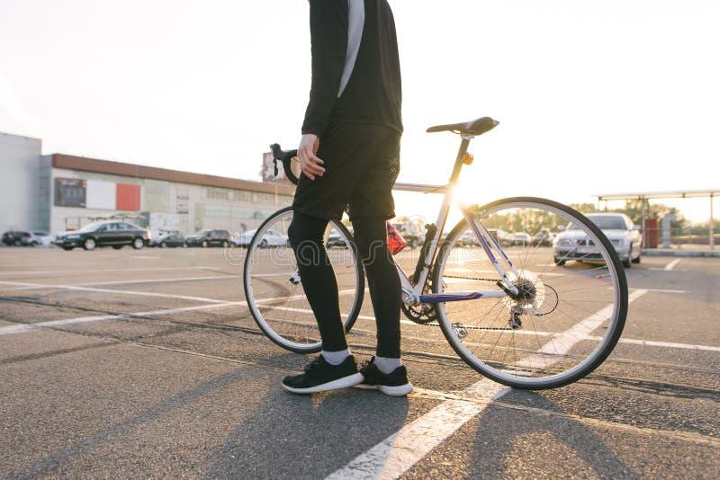 Fietser in donkere sportkleding met een wegfiets op de achtergrond van parkeren in de zonsondergang stock foto's