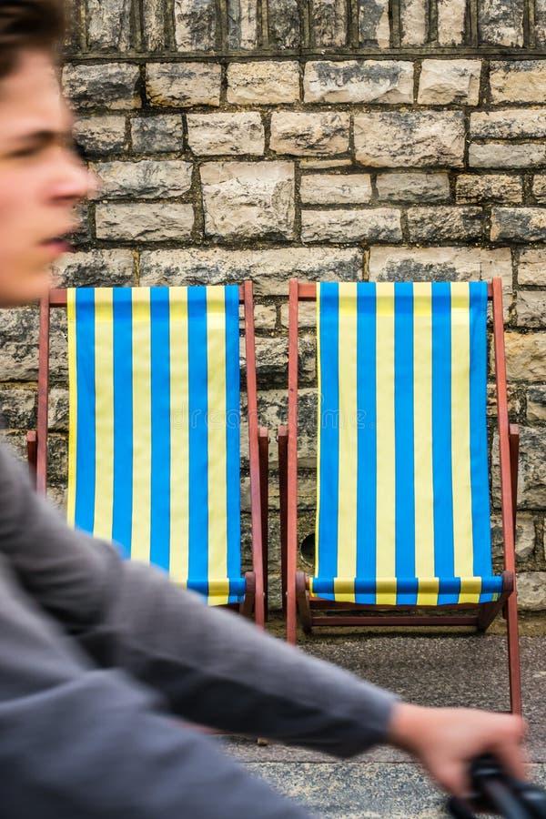 Fietser en deckchairs in kuststad royalty-vrije stock fotografie