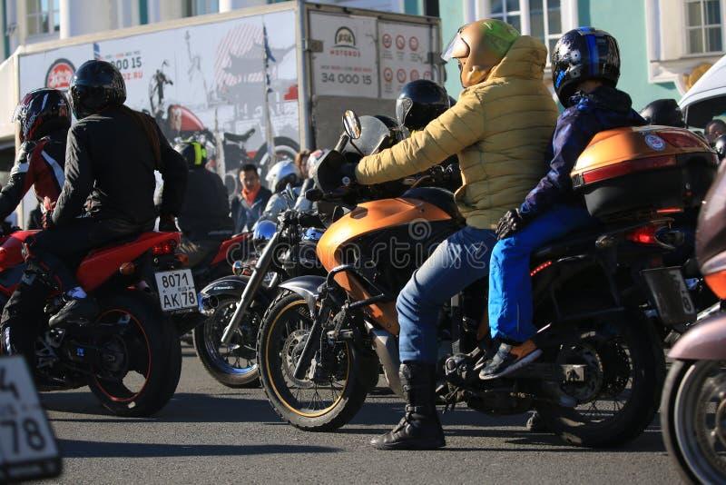 Fietser met een kind op zijn motorfiets onder andere fietsers royalty-vrije stock foto's
