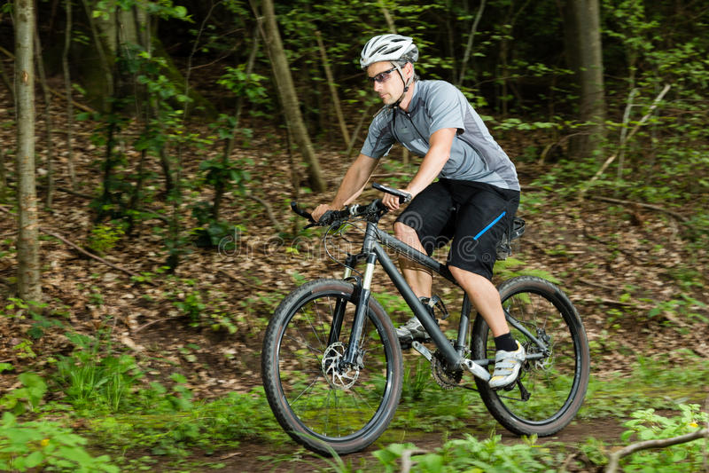 Fietser op een mountainbike in a bergaf stock fotografie