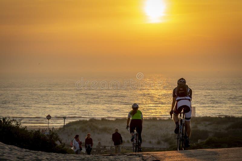 Fietser op het strand tijdens zonsopgang stock foto's