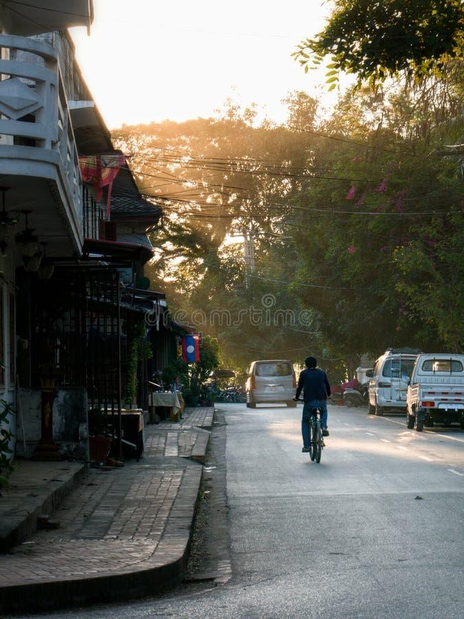 Fietser op kalme stadsweg in zonsonderganglicht royalty-vrije stock foto