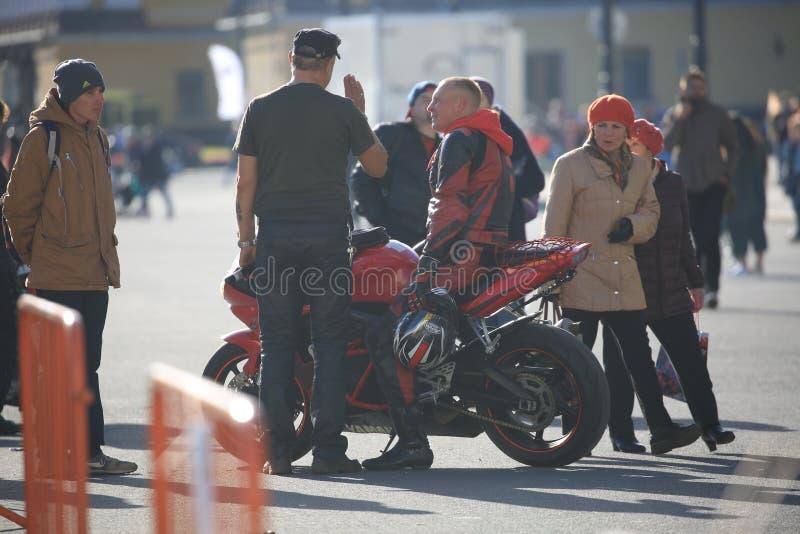 Fietser in rode en zwarte overall op zijn rode fiets onder mensen royalty-vrije stock afbeelding