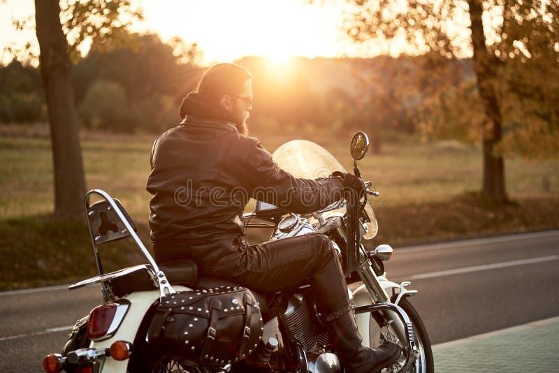 Fietser in zwarte leeruitrusting die moderne krachtige motorfiets langs zonnige weg op de zomerdag drijven royalty-vrije stock fotografie