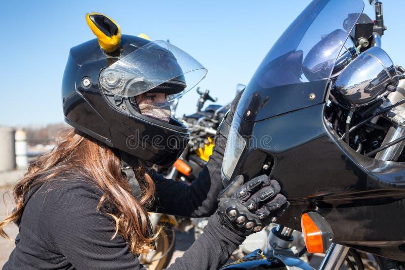 Fietsermeisje die in helm in koplamp van haar fiets en wat betreft plastic voorkap kijken royalty-vrije stock foto's