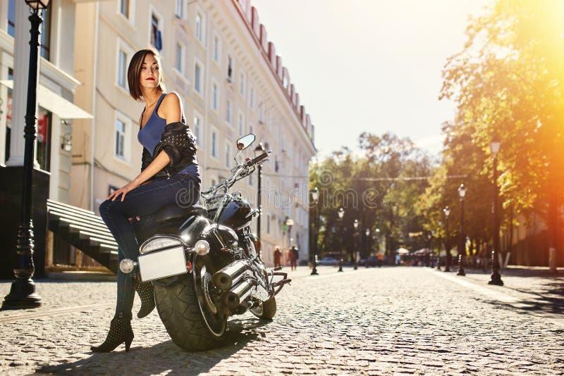 Fietsermeisje in een leerjasje op een motorfiets stock foto's
