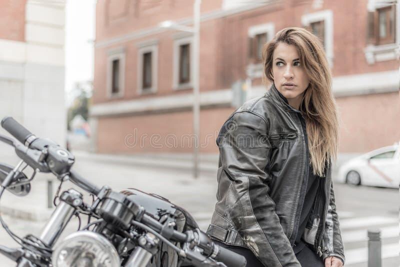 Fietsermeisje in een leerjasje op een motorfiets stock afbeeldingen