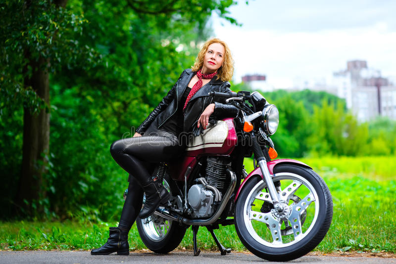 Fietsermeisje in leerjasje op een motorfiets stock fotografie