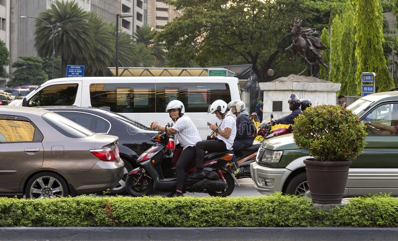 Fietsers en auto's die in verkeer in Manilla, Makati, Filippijnen wachten stock foto